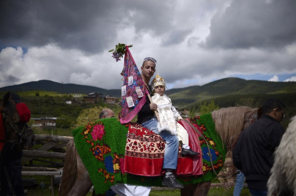 A Pomak man (an ethnic-Bulgarian of the Islamic faith) rides a  horse with his son during a mass circumcision ceremony for young boys in the  village of Draginovo, Bulgaria on May 4. More than 100 boys were circumcised  during a traditional ceremony.      NIKOLAY DOYCHINOV/AFP/Getty Images