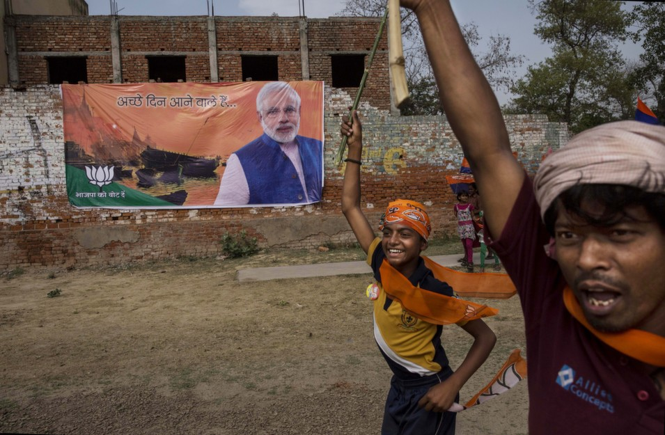 """Supporters run past a banner showing BJP leader Narendra Modi  in Rohaniya, near Varanasi, India, on May 8. Thousands of supporters later  lined the Hindu holy city as Modi drove to a party meeting after a rally he had  planned was prohibited by local authorities. India is in the midst of a  nine-phase election that began on April 7 and ends May 12. 's James Traub examines Modi's progress on the campaign trail in  his piece """"Watching Modi, the Maestro, at Work.""""      Kevin Frayer/Getty Images"""