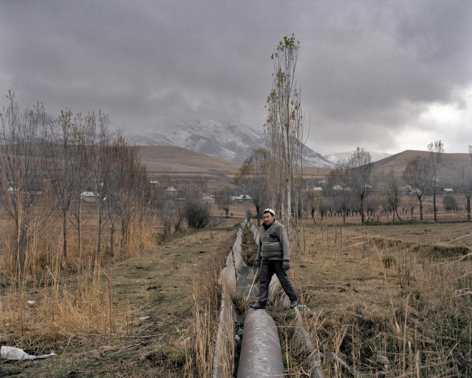 A man walks across the ruined gutter of an irrigation canal.      Fyodor Savintsev/Salt Images, 2012