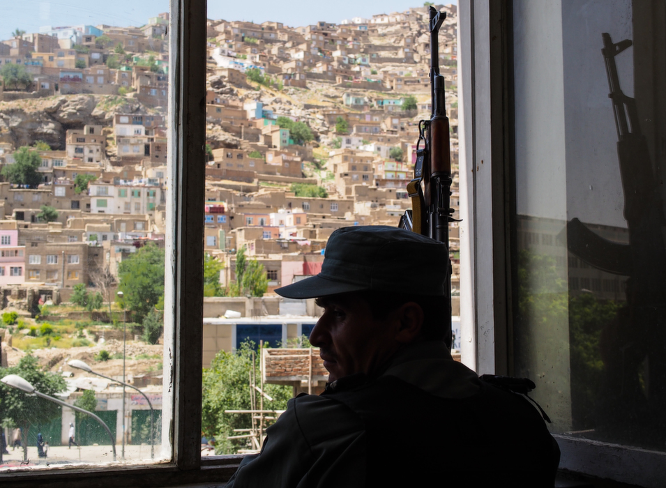 Inside police headquarters, an officer surveys the street for the arrival of  demonstrators supporting presidential candidate Abdullah Abdullah. They will  be protesting alleged voting fraud by supporters of presidential candidate  Ashraf Ghani.      Deni  Béchard