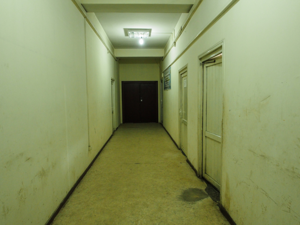A  hallway in the Kabul police station belies the high-tech monitoring operation being conducted inside; the walls are scuffed and linoleum floor  is peeling.      Deni  Béchard