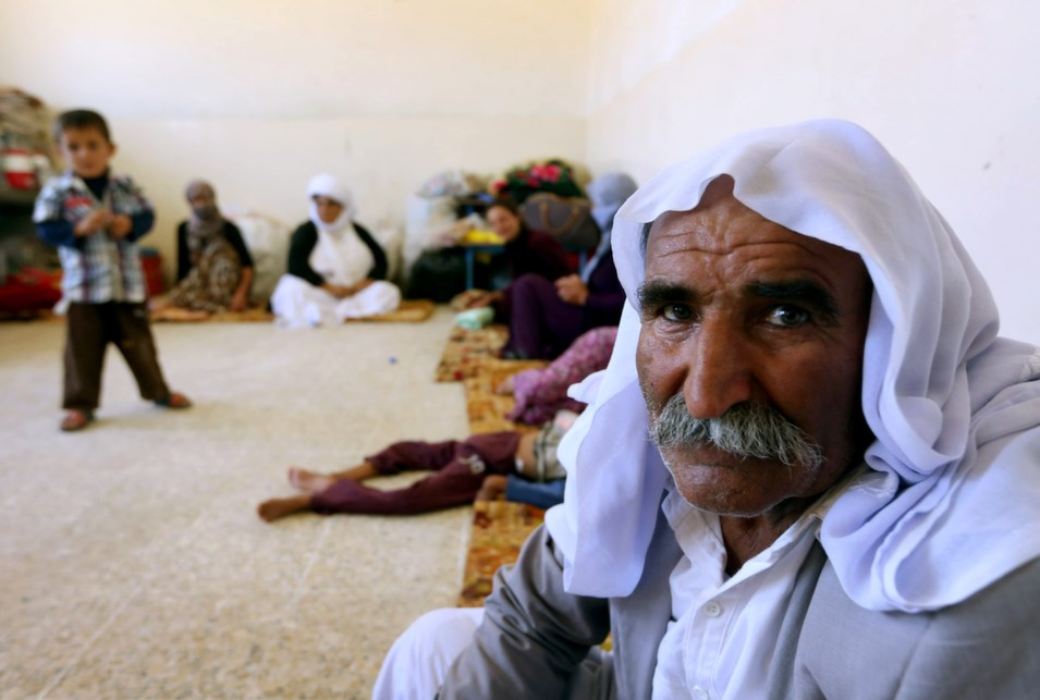 """On Sunday, as the  militants of the Islamic State rolled west from Mosul toward the city of  Sinjar, the ancestral home of the Yazidi people, thousands of members of the  ancient, persecuted religious community fled  their homes carrying whatever they could, to take shelter in the mountains.  As many as 40,000 Yazidis -- of the estimated 130,000 who escaped -- are now trapped on Mount Sinjar, where they sought refuge. With food and water  supplies running low,  they will not be able to sustain their position for long; but should they descend, death or forced conversion await.      Attendants of an 11th-century  religion that combines elements of Zoroastrianism, Islam, and Christianity,  the Kurdish-speaking Yazidis have been targeted by the Islamic State for  extermination. As theGuardian reports,  local officials estimate that 500 Yazidis """"including 40 children,  have been killed in the past week.""""      On Thursday, the  Obama administration authorized  emergency humanitarian aid (the U.S. military dropped  5,300 gallons of fresh drinking water and food rations) as well as possible  airstrikes to break  the surrounding siege. The fighters of the Islamic State, Obama said,  """"have called for the systematic destruction of the entire Yazidi people,  which would constitute genocide.""""      In their history, the  Yazidis claim  that they have survived 72 attempts to wipe them from the earth. Their  religion, which calls for the worship of a fallen angel, has historically made  them a target of persecution. Now, with the world watching, they face one more.      Above, members of an Iraqi Yazidi family  that fled the violence in the northern Iraqi town of Sinjar sit together in the school  where they are taking shelter in Dohuk, on Aug. 5.      SAFIN HAMED/AFP/Getty  Images"""