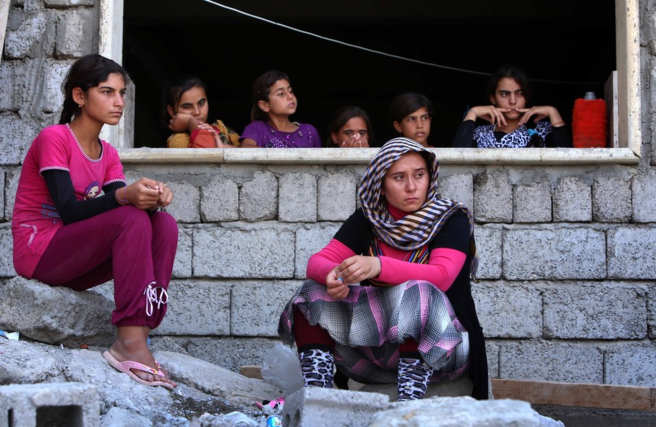 Yazidi women who fled  Sinjar sit at a school where they took shelter with thousands of others who  have fled violence in northern Iraq.      SAFIN HAMED/AFP/Getty  Images