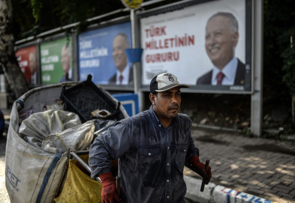 A man collecting rubbish walks past a campaign poster of Ekmeleddin Ihsanoglu, the leading opposition candidate for Turkish presidential elections, on Aug. 8.      Bulent Kilic AFP/Getty Images