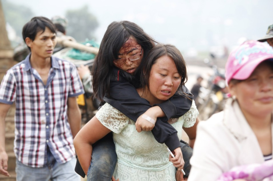 A woman carries an injured girl after the earthquake in Ludian county in Zhaotong, southwest China's Yunnan province on Aug. 4.       STR/AFP/Getty Images