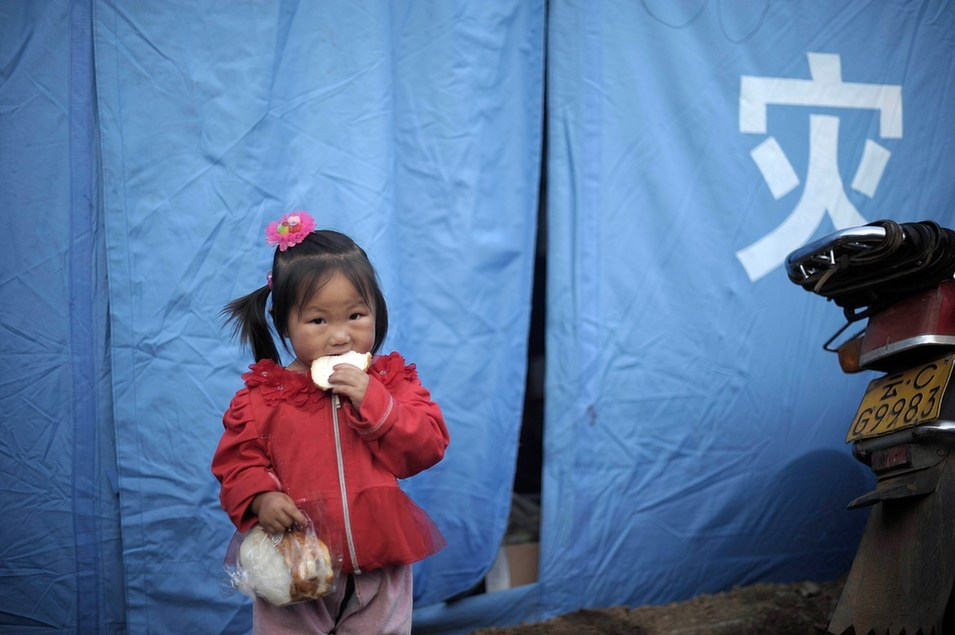 A young girl eats near a tent at a temporary shelter for earthquake victims in Longtoushan township of Ludian county in Zhaotong, southwest China's Yunnan province on August 6.       AFP/AFP/Getty Images