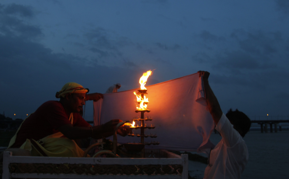 Men hold a cloth to protect the lit oil lamp from the wind, before offering Maa Ganga evening aarti on the river bank of Ganga in Allahabad. The aarti, is a devotional ritual that uses fire as an offering, it may be in form of a lit lamp, or a small diya with a candle and flowers that are floated down the river.      Ravi Prakash/Pacific Press/LightRocket via Getty Images