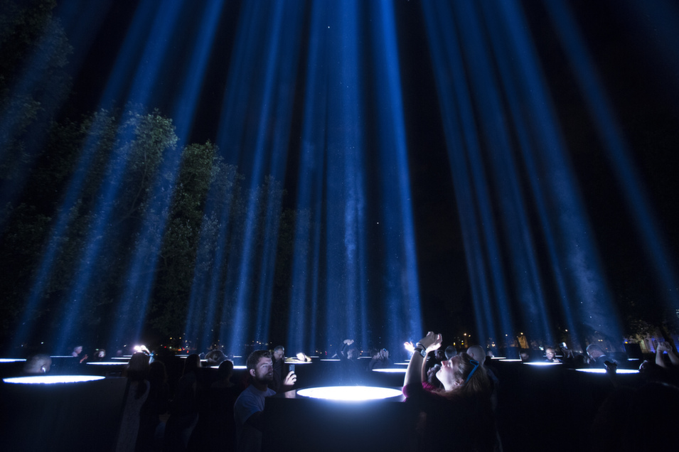 "Members of the public admire an art installation entitled ""spectra"" by Japanese artist Ryoji Ikeda which lights up the night sky as part of ""Lights Out,"" to commemorate the centenary of Britain's involvement in the First World War, on Aug. 4 in London.       Photo by Oli Scarff/Getty Images"
