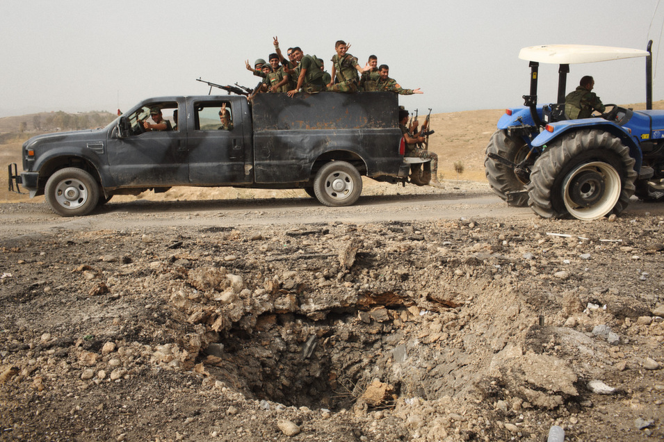 A  pickup truck full of Kurdish Peshmerga forces drives by a crater caused by a  U.S. airstrike not far from Mosul dam. They are on their way to continue the fight against IS to push their forces back  toward Mosul.