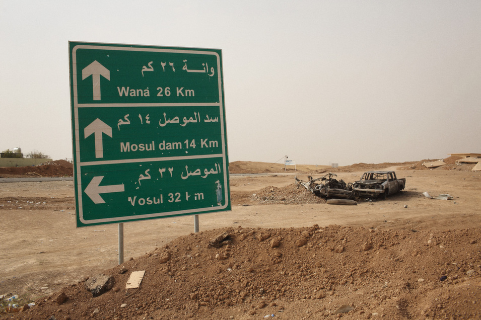A road  sign near Mosul dam. Cars destroyed in the offensive to push IS forces back from the dam and toward Mosul sit charred and idle on the side of the road.