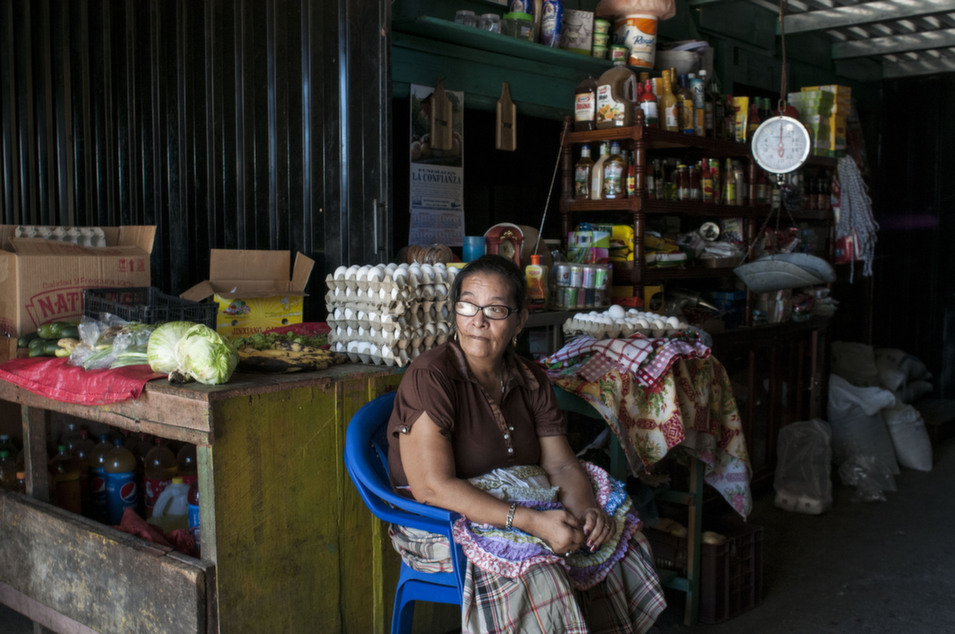 A small-business owner sits in her Amapala food store, which sells grains, snacks, and other provisions.