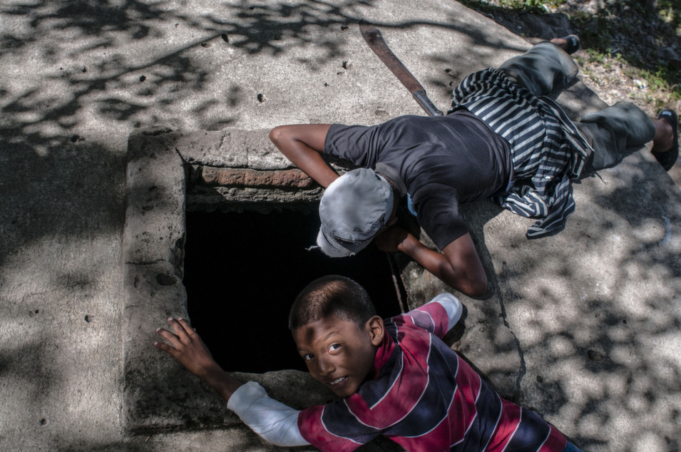 Two brothers look at a well in Puerto Grande, Amapala.