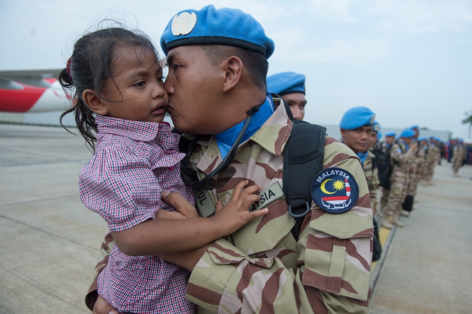 A member of the Malaysian armed forces kisses his daughter at an air base near Kuala Lumpur before leaving for Lebanon to serve with the United Nations Interim Force there, on Sept. 4.      Mohd Rasfan/AFP/Getty Images