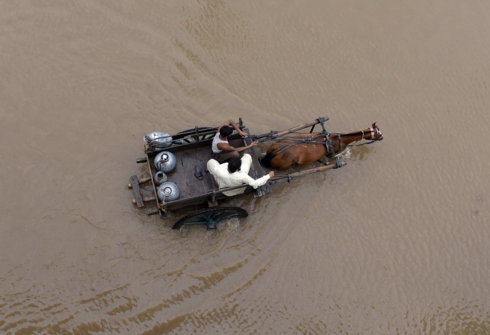 Pakistani milkmen ride a horse-cart through floodwaters following heavy rain in Lahore, on Sept. 4.       Arif Ali/AFP/Getty Images