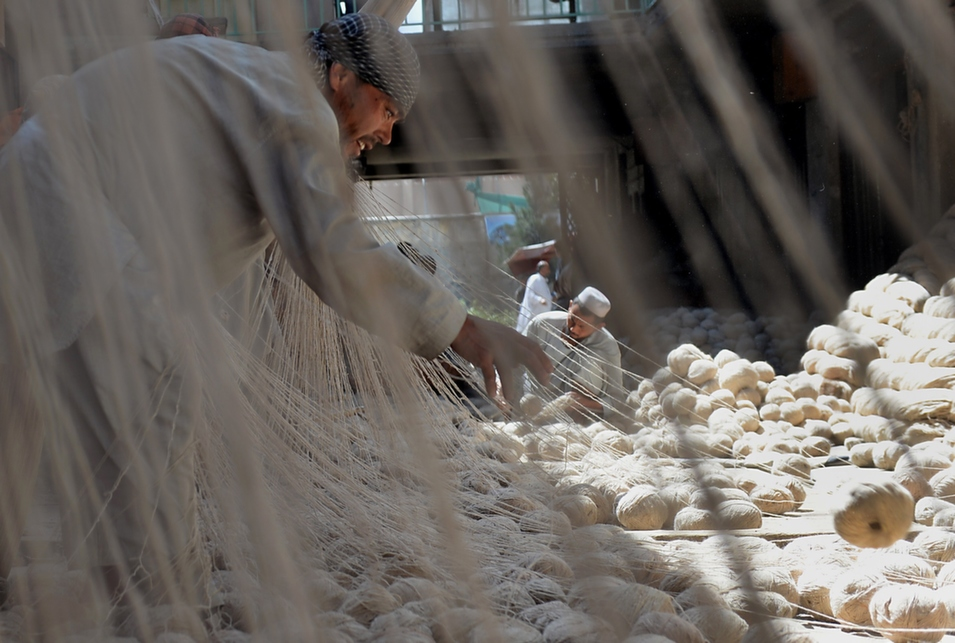 Afghan men sort carpet threads inside a traditional factory in Kabul, on Sept. 4. Foreign Policy contributor Nematullah Bizhan looked at the limits of U.S. aid in the country in a Sept. 4 article for FP's South Asia Channel.      Shah Marai/AFP/Getty Images