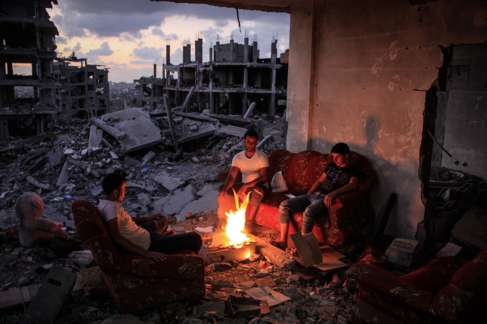 """Palestinians gather around a fire in the rubble of their house, shelled by Israel during Operation Protective Edge, in Gaza City, on Sept. 1. FP columnist Aaron David Miller examined the threat the Islamic State's expansion poses to the Israeli-Palestinian peace process in a Sept. 4 article, """"How the Islamic State Could Kill the Two-State Solution.""""      Ahmed Hjazy/Pacific Press/LightRocket via Getty Images"""