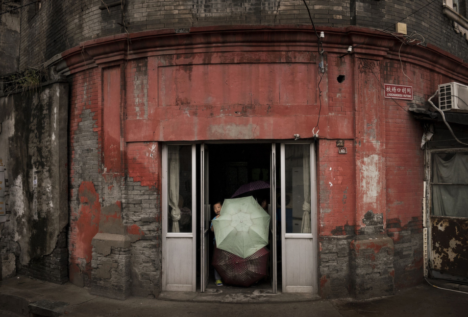 A Chinese boy holds umbrellas in the doorway of his house on a rainy day in Beijing, on Sept. 2.      Kevin Frayer/Getty Images