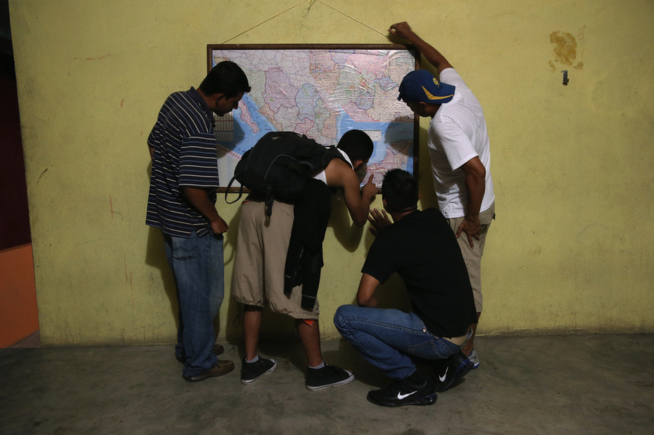 Honduran migrants inspect a map of Mexico at a shelter for undocumented immigrants in Tenosique, Mexico, Sept. 14. The shelter, called La 72, is run by Franciscan friars and is the first stop for thousands of Central American immigrants crossing through Mexico to reach the United States.       John Moore/Getty Images