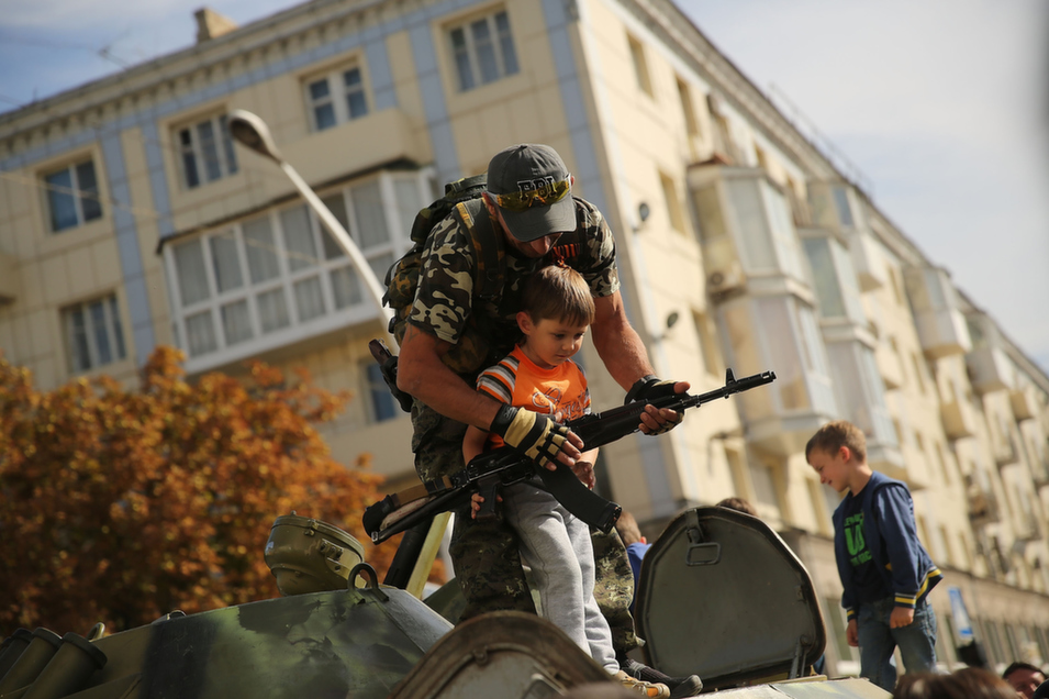 A separatist soldier shows a child a gun during a city celebration in Luhansk, Ukraine, Sept. 14. Alec Luhn reported for Foreign Policy from Luhansk, where residents have taken advantage of a tenuous lull in fighting to assess the damage suffered by their city -- and to slowly return to the patterns of daily life.       Spencer Platt/Getty Images