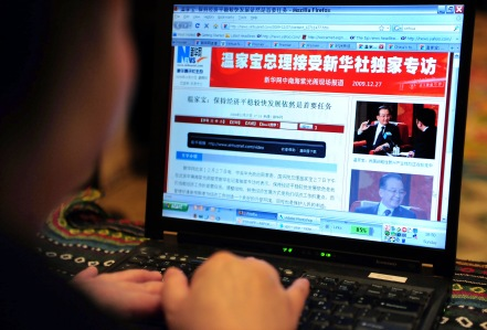 A woman reads the webpage as Chinese Pri