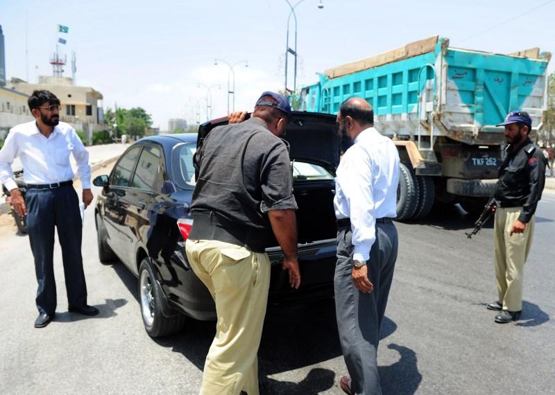 Pakistani police search a car at a roadb