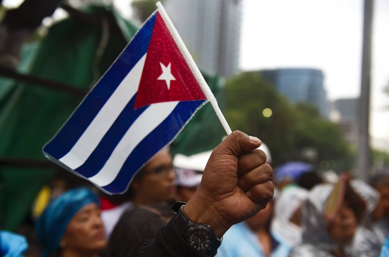 A man raises his fist with a Cuban flag