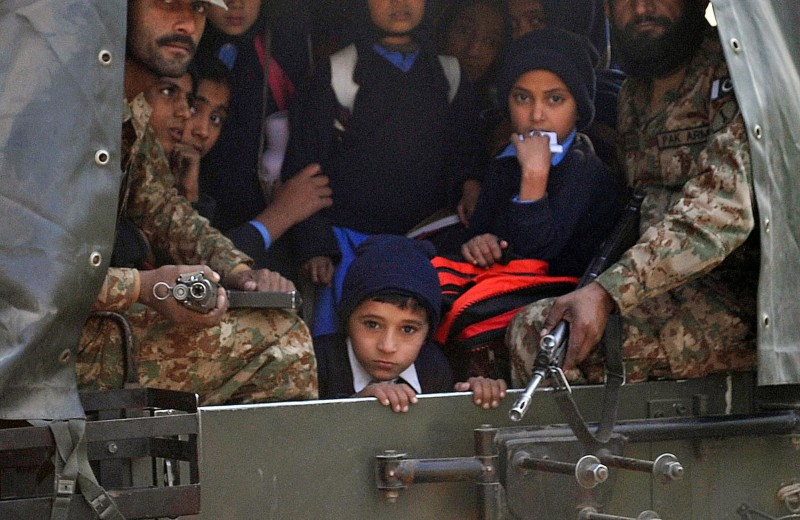 Pakistani soldiers transport rescued school children from the site of an attack by Taliban gunmen on a school in Peshawar on December 16, 2014. Taliban insurgents killed at least 130 people, most of them children, after storming an army-run school in Pakistan December 16 in one of the country's bloodiest attacks in recent years. AFP PHOTO/ A MAJEED        (Photo credit should read A Majeed/AFP/Getty Images)
