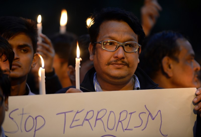 Indian shooter Jaspal Rana holds a burning candle as he pay tribute to Pakistan children and staff killed in a Taliban attack on a school in Peshawar, in New Delhi on December 17, 2014.  Pakistan began three days of mourning on December 17 for the 132 schoolchildren and nine staff killed by the Taliban in the country's deadliest ever terror attack as the world united in a chorus of revulsion.  AFP PHOTO / Prakash SINGH        (Photo credit should read PRAKASH SINGH/AFP/Getty Images)
