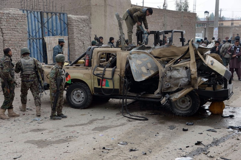 Afghan National Army (ANA) soldiers inspect a damaged army ranger vehicle at the site of a remote-controlled bomb blast in Jalalabad on December 21, 2014.  Two remote-controlled bombs hit a military vehicle in Jalalabad city in the east of Afghanistan, killing two and wounding two others, Ahmad Zia Abdul Zai, the provincial spokesman said.   AFP PHOTO / Noorullah Shirzada        (Photo credit should read Noorullah Shirzada/AFP/Getty Images)