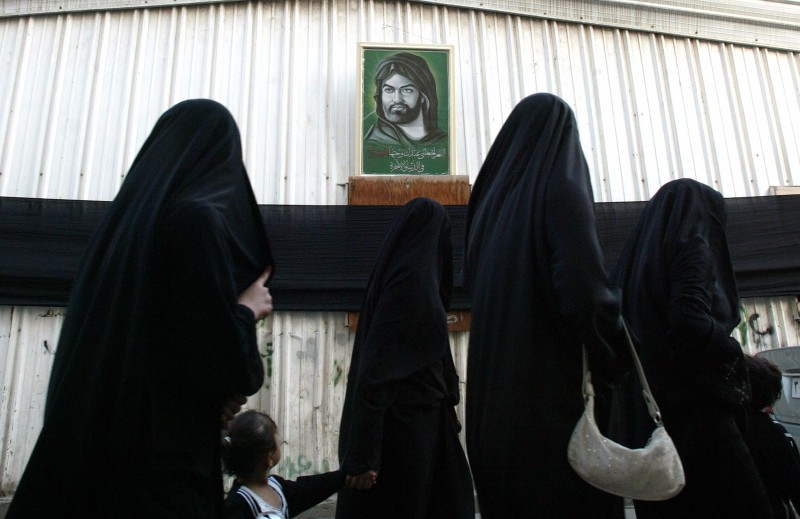 Saudi Shiite women walk past a portrait