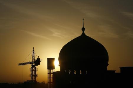 The sun rises behind a construction cran