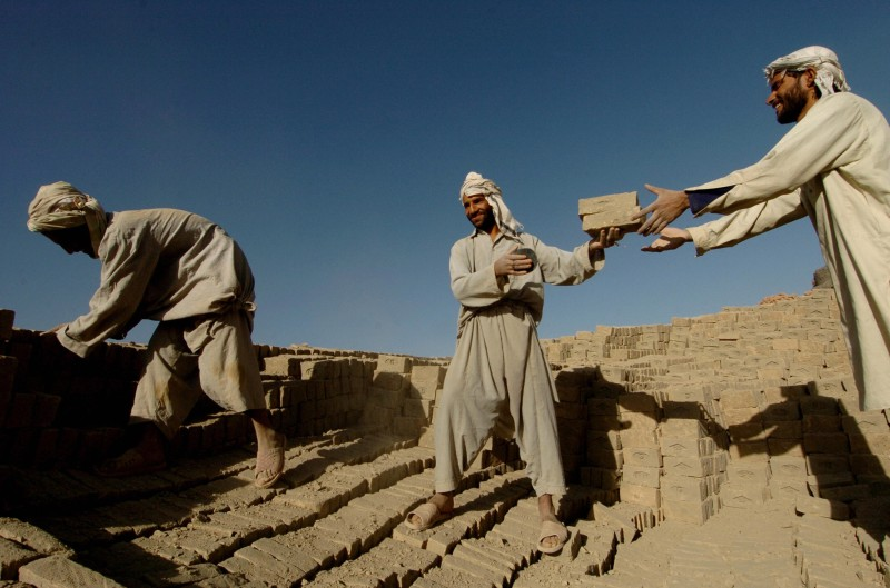 Afghan workers unload bricks from a kiln