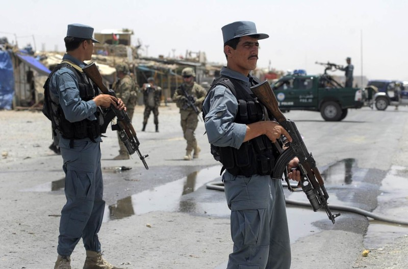 Afghan policemen stand guard as two US s