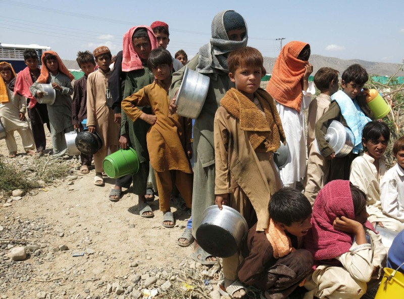 Internally-displaced Pakistani children whose families fled a military operation against Taliban militants in the North Waziristan tribal agency queue at a food distribution point near a camp for the internally-displaced in Bannu, near the North Waziristan border, on September 6, 2014. Pakistan's military said on September 3, 2014 it had killed more than 900 militants and lost 82 soldiers since the start of a major operation against the Taliban in the tribal northwest in June 2014. The military began a long-awaited push to clear insurgent bases from North Waziristan district, on the Afghan border, after a bloody attack on Karachi airport finally sank stuttering peace talks with the rebels. AFP PHOTO / KARIM ULLAH        (Photo credit should read KARIM ULLAH/AFP/Getty Images)