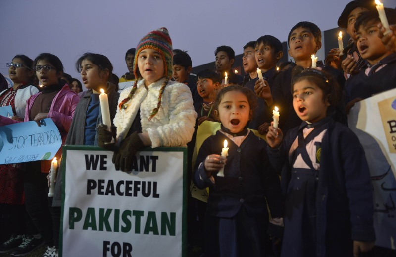 Pakistani civil society activists and children hold light candles during a vigil in Lahore on December 18, 2014, for the children and teachers killed in an attack by militants on an army-run school in Peshawar. Students grieving for their classmates massacred by the Pakistani Taliban have vowed to defy the militants and return to school as soon as possible. AFP PHOTO / Arif ALI        (Photo credit should read Arif Ali/AFP/Getty Images)