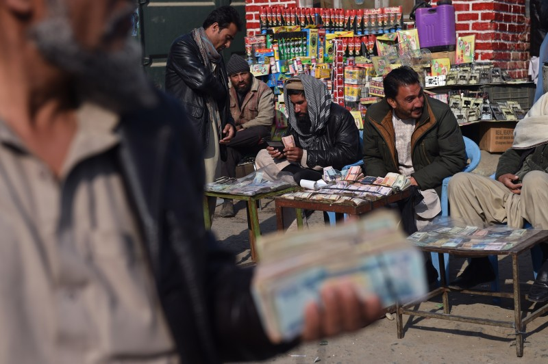 In this photograph taken on December 29, 2014, an Afghan customer (2nd L) counts his Afghani currency notes at a currency exchange market along the roadside in Kabul.  The Taliban insurgency may still be raging but the poor state of the economy could pose a bigger threat to Afghanistan's long-term viability, and huge mineral reserves are unlikely to offer a quick fix. In Kabul's Sarayee Shahzada market, moneychangers wave thick bundles of Afghanis, dollars, rupees and dirhams, but the customers are not packing the alleyways like they used to and business is well down on two years ago.       AFP PHOTO / Wakil Kohsar        (Photo credit should read WAKIL KOHSAR/AFP/Getty Images)