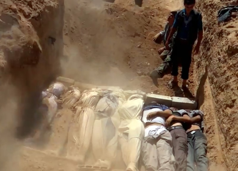 "An image grab taken from a video uploaded on YouTube by the Local Committee of Arbeen on August 21, 2013 allegedly shows Syrians covering a mass grave containing bodies of victims that Syrian rebels claim were killed in a toxic gas attack by pro-government forces in eastern Ghouta and Zamalka, on the outskirts of Damascus. The allegation of chemical weapons being used in the heavily-populated areas came on the second day of a mission to Syria by UN inspectors, but the claim, which could not be independently verified, was vehemently denied by the Syrian authorities, who said it was intended to hinder the mission of UN chemical weapons inspectors. AFP PHOTO / YOUTUBE / LOCAL COMMITTEE OF ARBEEN== RESTRICTED TO EDITORIAL USE - MANDATORY CREDIT ""AFP PHOTO / YOUTUBE / LOCAL COMMITTEE OF ARBEEN"" - NO MARKETING NO ADVERTISING CAMPAIGNS - DISTRIBUTED AS A SERVICE TO CLIENTS - AFP IS USING PICTURES FROM ALTERNATIVE SOURCES AS IT WAS NOT AUTHORISED TO COVER THIS EVENT, THEREFORE IT IS NOT RESPONSIBLE FOR ANY DIGITAL ALTERATIONS TO THE PICTURE'S EDITORIAL CONTENT, DATE AND LOCATION WHICH CANNOT BE INDEPENDENTLY VERIFIED ==        (Photo credit should read DSK/AFP/Getty Images)"