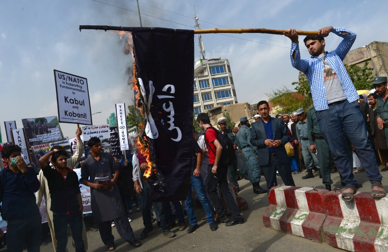 "Afghan Solidarity members burn an IS flag during a rally against the Islamic State (IS) group in Iraq and the US Presence in Afghanistan, in Kabul on October 12, 2014. Around 200 people, the demonstrators mostly women, chanted anti-IS and anti-US slogans as they rallied through downtown Kabul. The crowd carried placards reading ""US and NATO are supporting fundamentalism in Kabul and Kobani,"" and ""No NATO and US forces in Afghanistan.   AFP PHOTO/Wakil Kohsar        (Photo credit should read WAKIL KOHSAR/AFP/Getty Images)"