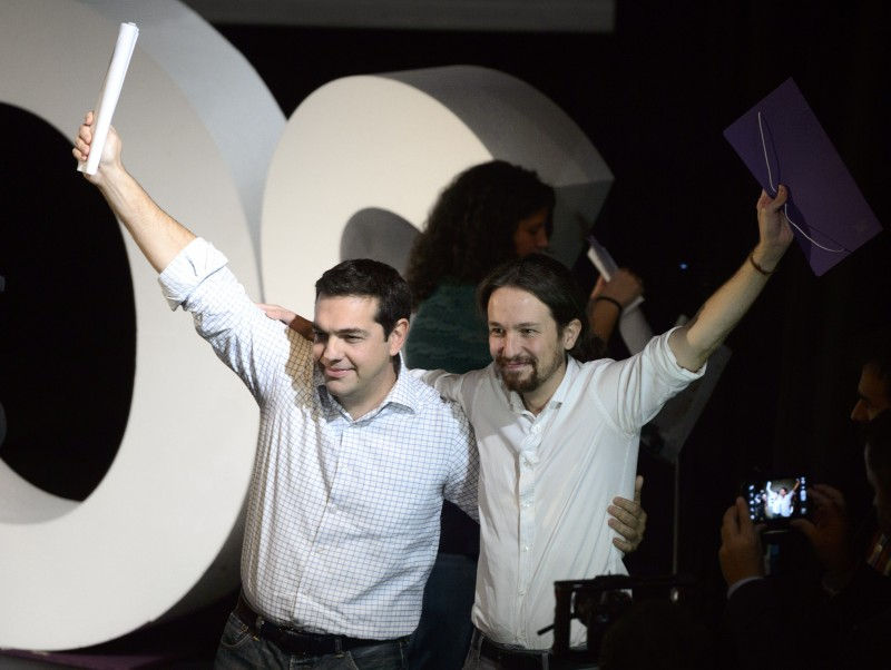 "President of Greek oposition SYRIZA (Coalition of the Radical Left) Alexis Tsipras (L) and newly confirmed leader of Podemos, a left-wing party that emerged out of the ""Indignants"" movement, Pablo Iglesias, wave at a party meeting in Madrid on November 15, 2014.  Podemos activists confirmed Pablo Iglesias, 36 years at the head of the movement, in a vote whose results were announced today. Pablo Iglesias was elected secretary general with 88.7% of the vote (95,311 votes out of 107,488) announced the party at a ceremony attended by nearly a thousand people in a Madrid theater.  AFP PHOTO / DANI POZO        (Photo credit should read DANI POZO/AFP/Getty Images)"