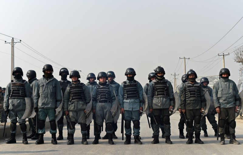 Afghan riot police stand guard at a protest against the printing of satirical sketches of the Prophet Muhammad by French magazine Charlie Hebdo along the Kabul-Jalalabad road in Kabul on January 31, 2015.    Around 500 protesters staged demonstrations in Hoodkhail district of Kabul during which protestors threw stones at the police forces at the site, but the police fired some gunshots in the air to stop them, Hashmat Stanikzai, Kabul police spokesman told AFP.  AFP PHOTO / WAKIL KOHSAR        (Photo credit should read WAKIL KOHSAR/AFP/Getty Images)