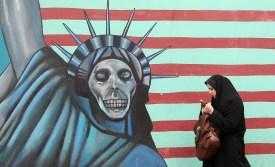 An Iranian woman walks past an anti-US m