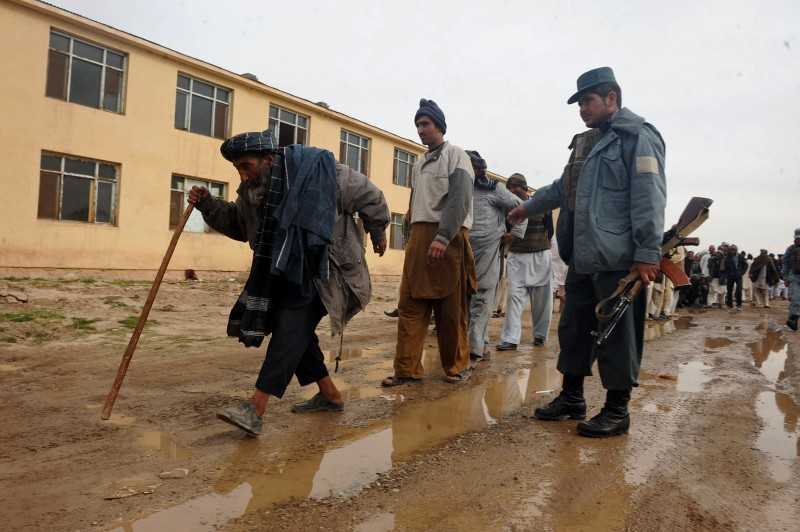 Former Afghan drug addicts walk down a dirt road after receiving two moths treatment at an Afghanistan Ministry of Counter Narcotics centre  in Herat on January 28, 2013. Afghan police and health officials collected 350 addicts from the streets of Herat and forced them to stay in a centre to receive treatment for two months. 130 were released after they stopped using and were ready to go back to society, police and health officials said.  AFP PHOTO/ Aref Karimi        (Photo credit should read Aref Karimi/AFP/Getty Images)