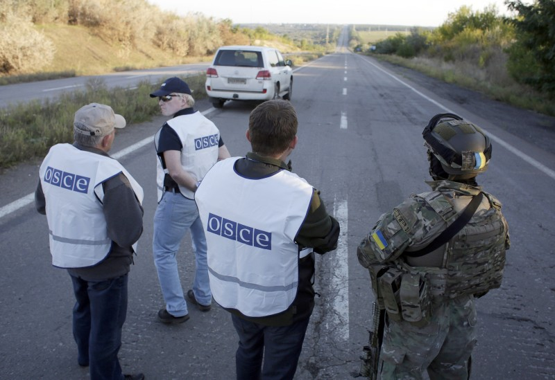 A Ukrainian serviceman (R) and OSCE observers wait on a road near Donetsk on September 20, 2014 before an exchange of captives, which are being freed under the terms of a ceasefire deal between Kiev and the separatist forces. The Ukrainian side handed over 38 insurgents in exchange for 34 captives. NATO's top military commander expressed cautious optimism on September 20 that a tenuous Ukrainian ceasefire whose details were thrashed out in marathon overnight negotiations would help end a bloody pro-Kremlin uprising that has inflamed East-West ties. AFP PHOTO/ANATOLII STEPANOV        (Photo credit should read ANATOLII STEPANOV/AFP/Getty Images)