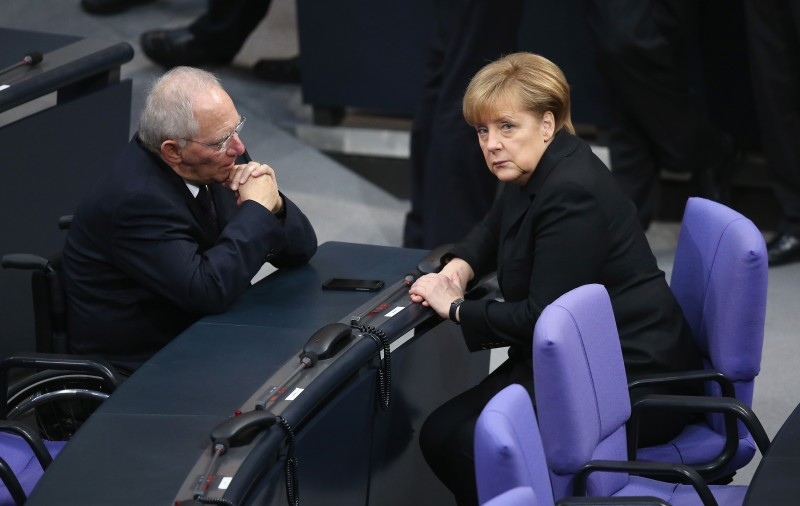 BERLIN, GERMANY - DECEMBER 17:  German Chancellor Angela Merkel (R) and Finance Minister Wolfgang Schaeuble chat during a vote at the Bundestag over her third term as chancellor during ceremonies in which the new German government will be sworn in on December 17, 2013 in Berlin, Germany. The new government is a coalition between the German Christian Democrats (CDU), the Bavarian Christian Democrats (CSU) and German Social Democrats (SPD) following federal elections held in September.  (Photo by Sean Gallup/Getty Images)