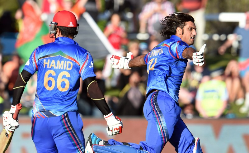 Afghanistan batsman Shapoor Zadran (R) celebrates with teammate Hamid Hassan (L) after hitting the winning runs to defeat Scotland in their 2015 Cricket World Cup Group A match in Dunedin on February 26, 2015.    AFP PHOTO / William WEST        (Photo credit should read WILLIAM WEST/AFP/Getty Images)