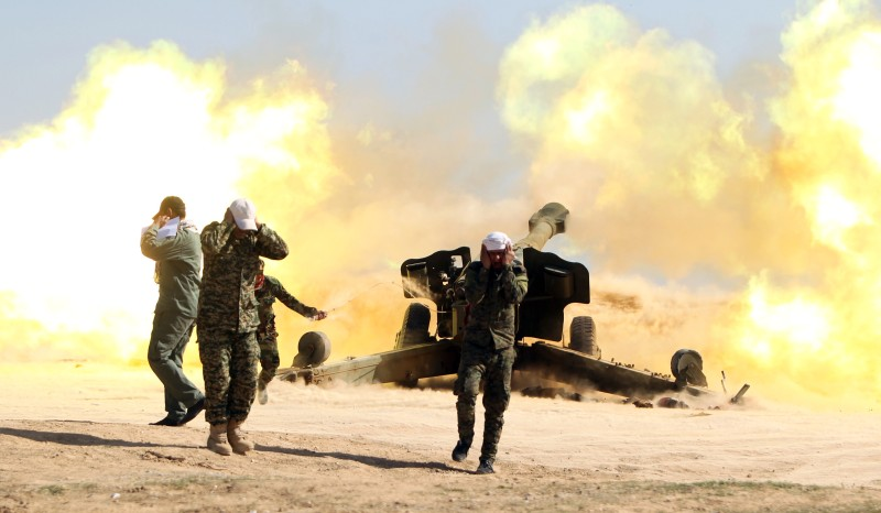 Volunteer Shiite fighters, known as the Popular Mobilisation units, who support the Iraqi government forces in the combat against the Islamic State (IS) group fire a Howitzer artillery canon in the village of Awaynat near the city of Tikrit on February 28, 2015. Government forces have attempted and failed several times to wrest back Tikrit -- the hometown of former president Saddam Hussein -- since losing it to IS in June 2014. AFP PHOTO/AHMAD AL-RUBAYE        (Photo credit should read AHMAD AL-RUBAYE/AFP/Getty Images)