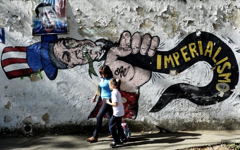 "A woman and a girl walk in front of a graffiti of US Uncle Sam in Caracas on March 11, 2015. Venezuelan President Nicolas Maduro moved closer Wednesday to ruling by decree after the legislature held a first vote that would allow him to act against ""external or internal"" threats to peace. AFP PHOTO / FEDERICO PARRA        (Photo credit should read FEDERICO PARRA/AFP/Getty Images)"