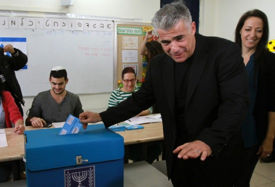 Israeli MP and chairperson of center-right Yesh Atid party, Yair Lapid, casts his ballot at a polling station with his wife Lihi (R) on March 17, 2015 in Tel Aviv. Voting polls opened for unpredictable elections to determine whether Israelis still want incumbent Prime Minister Benjamin Netanyahu as leader, or will seek change after six years. AFP PHOTO / GIL COHEN MAGEN        (Photo credit should read GIL COHEN MAGEN/AFP/Getty Images)
