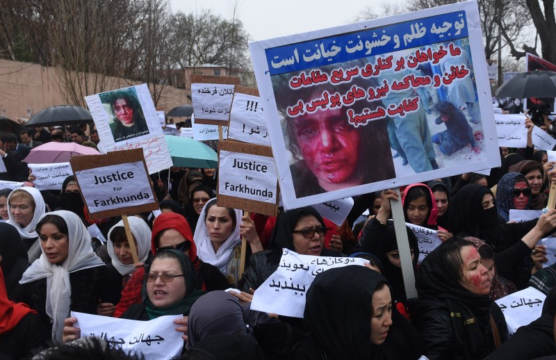 Afghan protesters hold banners as they shout slogans during a rally in front of The Supreme Court in Kabul on March 24, 2015, held to protest the killing of Afghan woman Farkhunda. More than a thousand people protested in the Afghan capital to call for justice after a woman was brutally killed by a mob who falsely accused her of burning a copy of the Koran. The woman, 27 year-old Farkhunda, was beaten with sticks and stones and thrown from a roof before being run over by a car outside a mosque in Kabul on March 19, 2015. The mob then set her body ablaze and dumped it in Kabul river, while police allegedly looked on. AFP PHOTO / SHAH Marai        (Photo credit should read SHAH MARAI/AFP/Getty Images)
