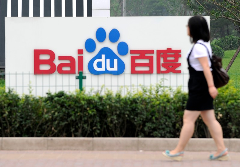 A woman walks past the logo of Baidu at
